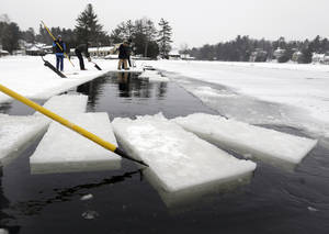Photo - A volunteer moves blocks of ice that have been cut from Lake Flower that will be used for the Saranac Lake Winter Carnival ice palace on Monday, Jan. 28, 2013, in Saranac Lake, N.Y. (AP Photo/Mike Groll)
