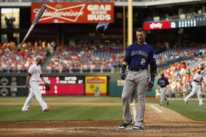 Photo - Colorado Rockies' Troy Tulowitzki, right, tosses his bat and helmet after striking out against Philadelphia Phillies relief pitcher Mike Adams to end the seventh inning of a baseball game, Monday, May 26, 2014, in Philadelphia. Philadelphia won 9-0. (AP Photo/Matt Slocum)