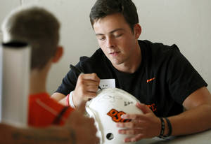 Photo - OKLAHOMA STATE UNIVERSITY / OSU / COLLEGE FOOTBALL: OSU quarterback Wes Lunt autographs a helmet during OSU Fan Appreciation Day at Gallagher-Iba Arena in Stillwater, Okla., Saturday, Aug. 4, 2012. Photo by Nate Billings, The Oklahoman