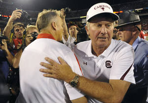 Photo -   FILE - In this Sept. 10, 2011, file phot, South Carolina coach Steve Spurrier, right, and Georgia coach Mark Richt meet at midfield after the Gamecocks on 45-42 in an NCAA college football game in Athens, Ga. Coaches you'd want on the sidelines of the biggest games? South Carolina's Steve Spurrier would have to be near the top of the very short list in college football. He gets the latest chance to enhance that reputation when the sixth-ranked Gamecocks take on No. 5 Georgia on Saturday. (AP Photo/John Amis, File)