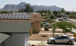 Photo - FILE - In this April 25, 2009 file photo, solar panels can be seen on the roofs of homes in this Apache Junction, Ariz., housing development. A lawsuit filed by two solar companies asks an Arizona court to overturn state tax officials' 2013 decision that homeowners leasing panels that produce electricity must pay property taxes. The interpretation said the homeowners' leased panels are subject to taxes like renewable energy generation equipment owned by large and medium-sized utilities. (AP Photo/East Valley Tribune, Darryl Webb, File   ARIZONA REPUBLIC OUT