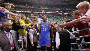 Photo - Fans reach for Oklahoma City Thunder's Kevin Durant (35) at the end of an NBA basketball game against the Utah Jazz, Tuesday, April 9, 2013, in Salt Lake City. The Thunder won 90-80. (AP Photo/Rick Bowmer) ORG XMIT: UTRB113