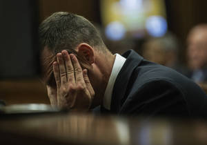 Photo - Oscar Pistorius cradles his head in his hands as he listens to evidence during his murder  trial in Pretoria, South Africa, Thursday, May 8, 2014. Pistorius is charged with the shooting death of his girlfriend Reeva Steenkamp on Valentine's Day in 2013. (AP Photo/Gianluigi Guercia, Pool)