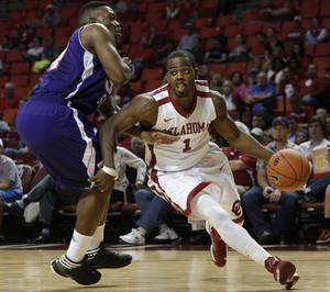 photo - OU: Oklahoma's Sam Grooms drives the ball past Northwestern's Gary Roberson (34) during a men's college basketball game between the University of Oklahoma and Northwestern Louisiana State University at the Lloyd Noble Center in Norman, Okla., Friday, Nov. 30, 2012.  Photo by Garett Fisbeck, The Oklahoman