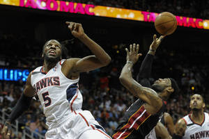 Photo - Miami Heat forward LeBron James, front right, is fouled under the basket by Atlanta Hawks forward DeMarre Carroll (5) during the first half of an NBA basketball game on Saturday, April 12, 2014, in Atlanta. (AP Photo/John Amis)