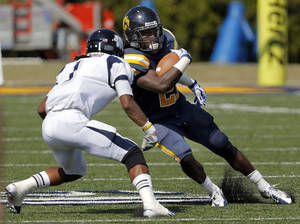 Photo - UCO's Joshua Birmingahm tries to get by Washburn's Devon Connors during the college football game between the University of Central Oklahoma and Washburn at Wantland Stadium in Edmond, Okla., Saturday, Sept. 22, 2012.  Photo by Sarah Phipps, The Oklahoman
