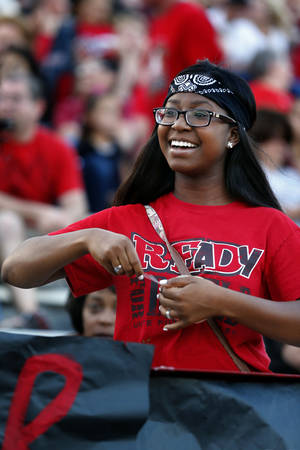 Photo - Carl Albert High School senior Tara Satterwhite tapes a banner to the stands before a high school football game between the Carl Albert Titans and the Deer Creek Antlers. Photo by Steve Sisney, The Oklahoman <strong>Steve Sisney - STEVE SISNEY</strong>