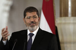 Photo -   FILE - In this Friday, July 13, 2012 file photo, Egyptian President Mohammed Morsi speaks to reporters during a joint news conference with Tunisian President Moncef Marzouki, unseen, at the Presidential palace in Cairo, Egypt. An Egyptian presidential official said Saturday, Aug. 18, 2012 that President Mohammed Morsi will attend a summit of non-aligned nations in Iran end of the month, in first such visit in decades.(AP Photo/Maya Alleruzzo, File)