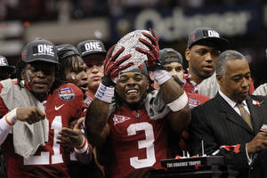 Photo - FILE - In this Jan. 9, 2012, file photo, Alabama running back Trent Richardson holds up the championship trophy after winning the BCS National Championship NCAA college football game against LSU, in New Orleans. College football may finally get a playoff system of sorts, if the rumblings out of the Big Ten this week are any indication of the current thought process. The conference that helped spike the idea of teams actually earning their spots in the national title game when it was proposed four years ago, seems to be warming up to it now. (AP Photo/Dave Martin, File) ORG XMIT: NY167