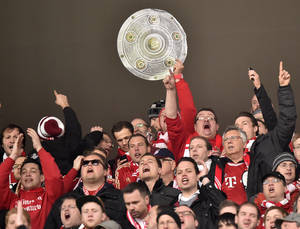 Photo - Bayern fans with a trophy celebrate during  the German Bundesliga soccer match between FSV Mainz 05 and Bayern Munich in Mainz,  Germany, Saturday, March 22, 2014. (AP Photo/Martin Meissner)