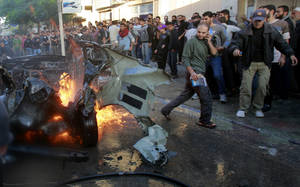 photo -   People look at a wreckage of the car in which was killed Ahmed Jabari, head of the Hamas military wing in Gaza City, Wednesday, Nov. 14, 2012. The Israeli military said its assassination of the Hamas military commander marks the beginning of an operation against Gaza militants. (AP Photo/Adel Hana)