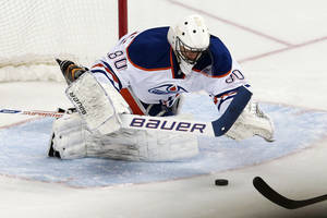 Photo - Edmonton Oilers goalie Ilya Bryzalov, of Russia, dives on a puck as he blocks a shot against the Nashville Predators in the second period of an NHL hockey game Thursday, Nov. 28, 2013, in Nashville, Tenn. (AP Photo/Mark Humphrey)