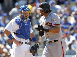 Photo - Los Angeles Dodgers catcher A.J. Ellis, left, watches as San Francisco Giants' Michael Morse, right, applauds at home plate after hitting a solo home run in the fourth inning in a baseball game on Saturday, April 5, 2014, in Los Angeles. (AP Photo/Alex Gallardo)