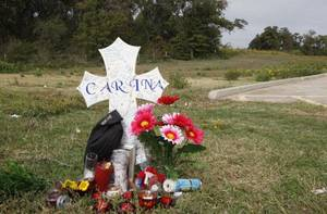 Photo - A memorial to Carina Saunders sits behind a grocery store in Bethany near the wooded area where her dismembered body was found stuffed in a duffel bag.  (AP Photo/Sue Ogrocki) ORG XMIT: OKSO102 <strong>Sue Ogrocki - AP</strong>