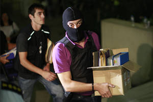 Photo - An anti-terror police officer carries a box containing the case file against the arrested suspects of the extreme far-right Golden Dawn party as he arrives at the court  in Athens, Saturday, Sept. 28, 2013. Police arrested the leader of Greece's extreme-right Golden Dawn party and other top members on Saturday, in an escalation of a government crackdown after a fatal stabbing allegedly committed by a supporter. It is the first time since 1974 that sitting members of Parliament have been arrested. (AP Photo/Kostas Tsironis)