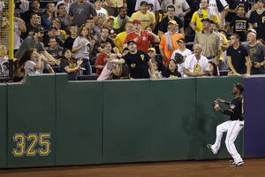 Photo - Pittsburgh Pirates left fielder Starling Marte watches as a home run by Cincinnati Reds' Joey Votto lands in the stands during the 10th inning of a baseball game in Pittsburgh on Friday, Sept. 20, 2013. The Reds won in 10 innings, 6-5. (AP Photo/Gene J. Puskar)