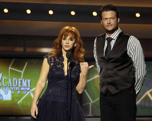 Photo -   FILE - This April 3, 2011 file photo shows hosts Reba McEntire, left, and Blake Shelton onstage at the 46th Annual Academy of Country Music Awards in Las Vegas. McEntire is ending her run as host of the Academy of Country Music Awards. She's stepping aside after a record 14 appearances, the last two with co-host Blake Shelton, who will return on the 2013 edition of the awards show. (AP Photo/Julie Jacobson, file)