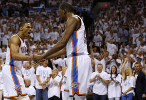 Photo - Oklahoma City Thunder's Russell Westbrook, left, and Kevin Durant (35) celebrate during the first half against the San Antonio Spurs in Game 6 of the Western Conference finals NBA basketball playoff series in Oklahoma City, Saturday, May 31, 2014. (AP Photo/Sue Ogrocki)