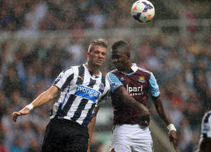 Photo - Newcastle United's Davide Santon, left, vies for the ball with West Ham United's Modibo Maiga, right, during their English Premier League soccer match at St James' Park, Newcastle, England, Saturday, Aug. 24, 2013. (AP Photo/Scott Heppell)