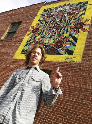 "Photo - Rick Sinnett is in front of ""Indian Warrior,"" his mural in the Blue Dome District of Tulsa. PHOTO PROVIDED"