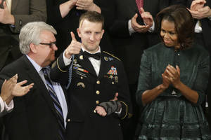 Photo - ** ADDS NAME OF FATHER AT LEFT ** Craig Remsburg, father of Army Ranger Sgt.1st Class Cory Remsburg, center, watches as his son acknowledges applause from first lady Michelle Obama and others during President Barack Obama's State of the Union address on Capitol Hill in Washington, Tuesday Jan. 28, 2014. (AP Photo/J. Scott Applewhite)