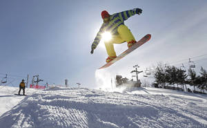 photo - FILE - In this Jan. 24, 2013 file photo, Mason Bemiller, 17, from Northridge High School in Middlebury, Ind., snowboards through the terrain park at Swiss Valley ski area in Jones, Mich. The lack of snow in some places, and in even places with snow that are getting less than usual, illustrates the increasingly fickle nature of winter in the Midwest, where dry, mild weather is making life difficult for businesses that rely on abundant snow. (AP Photo/Kalamazoo Gazette-MLive Media Group, Mark Bugnaski) ALL LOCAL TV OUT; LOCAL TV INTERNET OUT