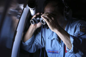 Photo - Vietnamese Air Force Col. Pham Minh Tuan uses binoculars on board a flying aircraft during a mission to search for the missing Malaysia Airlines flight MH370 in the Gulf of Thailand, Thursday, March 13, 2014. With no distress call, no sign of wreckage and very few answers, the disappearance of the Malaysia Airlines plane is turning into one of the biggest aviation mysteries since Amelia Earhart vanished over the Pacific Ocean in 1937. (AP Photo)