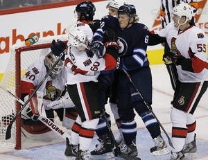Photo - Winnipeg Jets' Ryan Olsen (68) and Ottawa Senators' Troy Rutkowski (60) fight for position in front of Senators goaltender Robin Lehner (40) during the first period of a preseason NHL hockey game in Winnipeg on Sunday, Sept. 15, 2013. (AP Photo/The Canadian Press, John Woods)