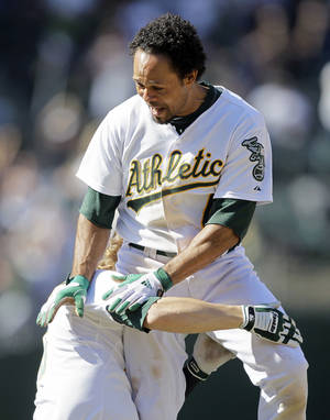 Photo -   Oakland Athletics' Coco Crisp is lifted by teammate Josh Reddick after driving in the winning run in the 12th inning of their baseball game against the New York Yankees, Sunday, July 22, 2012, in Oakland, Calif. Oakland won the game 5-4 to sweep their four-game series. (AP Photo/Eric Risberg)