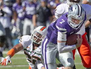 Photo -   Kansas State quarterback Collin Klein (7) gets away from Miami defensive back Kacy Rodgers II (22) during the first half of an NCAA football game in Manhattan, Kan., Saturday, Sept. 8, 2012. (AP Photo/Orlin Wagner)