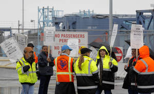 photo - Clerical workers picket in the rain at entrance to Pier 400 at the Port of Los Angeles Thursday, Nov. 29, 2012.  Cargo ships were stacking up at the ports of Los Angeles and Long Beach as a strike by about about 70 clerical workers shut down most of the terminals that together are the nation&#039;s busiest port complex.  Dockworkers were refusing to cross the picket lines even though an arbitrator ruled the walkout invalid on Tuesday.  By Thursday morning, at least 18 ships docked and inside the adjacent harbors were not being serviced, port spokesmen said. (AP Photo/Nick Ut)