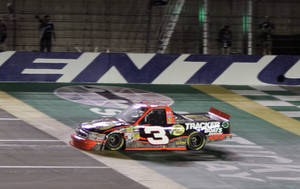 Photo - Ty Dillon crosses the finish line to win the NASCAR Truck Series auto race at Kentucky Speedway in Sparta, Ky., Thursday, June 27, 2013. (AP Photo/Garry Jones)