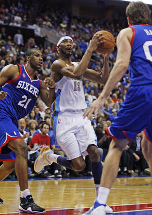 Photo -   Denver Nuggets' Corey Brewer (13) looks to shoot against Philadelphia 76ers' Thaddeus Young (21) and Spencer Hawes (00) in the first half of an NBA basketball game, Wednesday, Oct. 31, 2012, in Philadelphia. (AP Photo H. Rumph Jr)