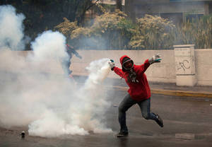 Photo - A demonstrator throws back a teargas canister fired by Bolivarian National Police after clashes broke out at an anti-government protest in Caracas, Venezuela, Thursday, May 8, 2014.  Demonstrators took to the streets after a pre-dawn raid by security forces that broke up four camps maintained by student protesters and arrested more than 200 people. The tent cities were installed more than a month ago in front of the offices of the United Nations and in better-off neighborhoods in the capital to protest against President Nicolas Maduro's socialist government. (AP Photo/Alejandro Cegarra)