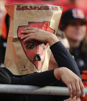 "Photo -   A Kansas City Chiefs fan wears a paper bag with ""Sorrowhead"" on it over his head as he watches the closing minutes of an NFL football game against the Cincinnati Bengals Sunday, Nov. 18, 2012, in Kansas City, MO. The Bengals won 28-6. The Chiefs have lost seven straight games. (AP Photo/Ed Zurga)"