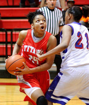 Photo - Carl Albert Lady Titans'  Gioya Carter drives against  Millwood  Lady Falcons Lauren Fonteno in the 2012 Titan Classic Basketball Tournament at Carl Albert High School,  Saturday, Jan. 21, 2012.   The Lady Titans won, 47-35.  Photo by Jim Beckel, The Oklahoman