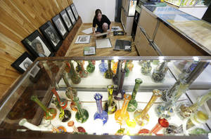 Photo - Krystal Klacsan prepares artwork to be hung, Monday, July 7, 2014 behind a case displaying glass bongs at the recreational marijuana store Cannabis City in Seattle. When legal sales begin on Tuesday, July 8, 2014, the store will be the first and only store in Seattle to initially sell recreational marijuana. (AP Photo/Ted S. Warren)