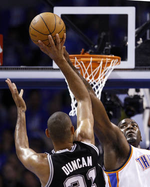 Photo - Oklahoma City's Kendrick Perkins, right, defends against San Antonio's Tim Duncan during Thursday's Game 3 of the Western Conference Finals at Chesapeake Energy Arena. The Thunder won 102-82 to cut the Spurs' series lead to 2-1. Photo by Sarah Phipps, The Oklahoman