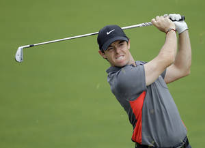 Photo - Rory McIlroy grimaces as he hits from the fairway to 16th green during the pro-am of the Wells Fargo Championship golf tournament at Quail Hollow Club in Charlotte, N.C., Wednesday, April 30, 2014. (AP Photo/Bob Leverone)
