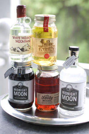 Photo - From top left clockwise, White Mountain Moonshine, FireFly Moonshine Apple Pie Flavor, Midnight Moon Moonshine, Ole Smoky Tennessee Moonshine Blackberry and Midnight Moon Blueberry are shown. AP PHOTO <strong>Matthew Mead - AP</strong>
