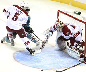Photo - Phoenix Coyotes goalie Mike Smith tracks the puck in front of the crease as Connor Murphy (5) checks a San Jose Shark during the first period of an NHL preseason hockey game in San Jose, Calif., Saturday, Sept. 21, 2013. (AP Photo/Mathew Sumner)