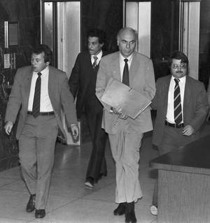 Photo - In this Jan. 22, 1983 file photo, ex-CIA agent Edwin Wilson, center, leaves federal court after a day of jury selection accompanied by U.S. Marshals in Houston. Edwin P. Wilson, a former CIA operative who was branded a traitor and convicted of shipping arms to Libya but whose conviction was later overturned after he served 22 years in prison, has died. AP File Photo <strong>Uncredited</strong>
