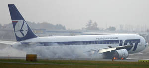 photo -   FILE - In this Tuesday, Nov. 1, 2011 file photo, a LOT airlines Boeing 767 makes an emergency landing at the Warsaw, Poland airport. The plane was en route from Newark with 230 people on board but no one was injured. Passengers on the plane that crash-landed in Poland when its landing gear failed to deploy have sued Boeing and the firm that inspected the airliner before it departed New Jersey, with one attorney saying his clients suffered severe emotional trauma from thinking they were about to die. A lawsuit claiming both physical and psychological damage was filed in November 2012 in Cook County Circuit Court in Chicago, where Boeing is headquartered, contends design flaws in the 767-300 led to fluid leaking from the hydraulic system. It said workers of New York-based Mach II Maintenance should have detected it. (AP Photo)