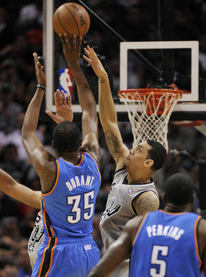 Photo - Kevin Durant, left, shoots over Danny Green in the first half Saturday night in San Antonio. AP Photo