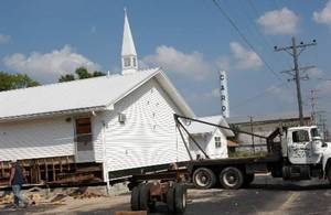 Photo - The former  Cardin Church getting prepared to be moved out of  Cardin and the superfund site on Monday afternoon by the Robin Hausner House Moving Company. By Gary Crow for The Oklahoman