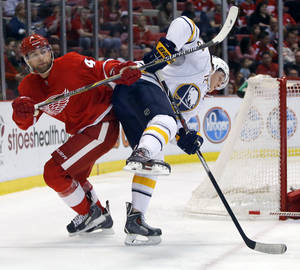 Photo - Detroit Red Wings' Jakub Kindl (4), of the Czech Republic, knocks Buffalo Sabres' Luke Adam (72) off-balance during the first period of an NHL hockey game Friday, April 4, 2014, in Detroit. (AP Photo/Duane Burleson)