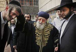 Photo - FILE - In this Feb. 10, 2009 file photo, Rabbi Ovadia Yosef, center, Jewish spiritual leader of Israel's Shas party, blesses a man after casting his ballot at a polling station in Jerusalem. An Israeli health official said Saturday Jan. 12, 2013, that influential Yosef has been hospitalized after feeling unwell. (AP Photo/Kevin Frayer, File)