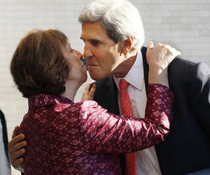 Photo - U.S. Secretary of State John Kerry, right, greets European Union Foreign Policy Chief Catherine Ashton after arriving for an informal meeting of EU ministers for Foreign Affairs at the National Art Gallery in Vilnius, Lithuania, Saturday, Sept. 7, 2013. (AP Photo/Mindaugas Kulbis)