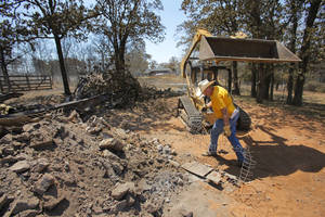 photo - Southern Baptist Convention volunteers Leo Furrh, removes fencing as Jim Howard operates a front end loader at a home on 130th Street in Noble on Monday. Photo By Steve Gooch, The Oklahoman <strong>Steve Gooch</strong>
