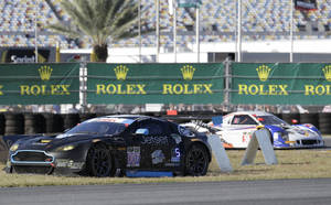 Photo - James Davison, left, of Australia, drives in the infield grass to get back on the track after a spinout in the horseshoe turn during  the IMSA Series Rolex 24 hour auto race at Daytona International Speedway in Daytona Beach, Fla., Saturday, Jan. 25, 2014.(AP Photo/John Raoux)